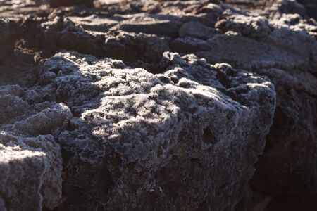 Thin layer of the frost on the lava stones in the cold spring morning in Teide National Park, creating various structure, enlightened by the sun. Tenerife, Canary Islands, Spain. Reklamní fotografie