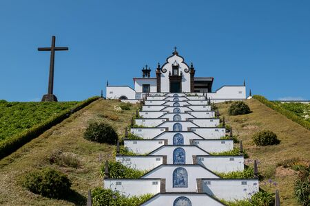 Hermitage (Ermitage de Nossa Senhora da Paz). White facade of the stairs and chapel, built in a hill, surrounded by park with green grass. Vila Franca do Campo, Sao Miguel, Azores Islands, Portugal.