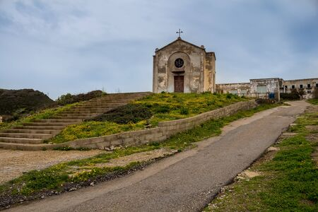 Church in former mining town. Old building with a weathered facade. View from the front. Argentiera, Sardinia, Italy.
