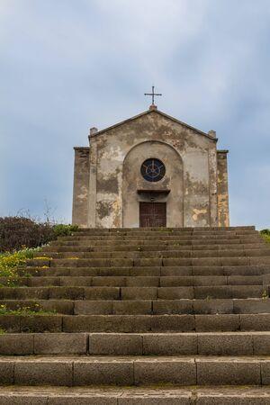 Kirche in ehemaliger Bergbaustadt. Altbau mit verwitterter Fassade. Ansicht von vorne. Argentiera, Sardinien, Italien.