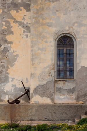 Old rusted anchor, used as a decoration outdoors. Weathered facade with a window of an old church in the background. Argentiera, Sardinia, Italy.