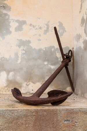 Old rusted anchor, used as a decoration outdoors. Weathered facade of an old church in the background. Argentiera, Sardinia, Italy.