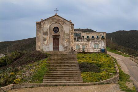 Kirche in ehemaliger Bergbaustadt. Altbau mit verwitterter Fassade. Ansicht von vorne. Argentiera, Sardinien, Italien. Standard-Bild