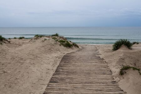 Calm morning beach in the spring. Wooden pathway between the sand dunes, lining the city beach. Horizon of the Mediterranean sea. Light clouds. Alghero, Sardinia, Italy.
