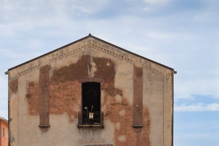 Detail of an old abandoned house with a weathered facade. Blue sky with intense white clouds. Bosa, Sardinia, Italy.