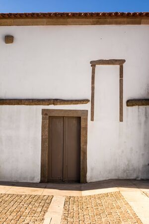 White weathered wall of a Chapel Boa Nova, with a wooden closed door, stone horizontal line and a part of an old window frame. Palmeira, Porto, Portugal.