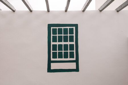 White facade of a wall with dark green painted traditional window. Square in Arico Nuevo, Tenerife, Canary Islands, Spain.