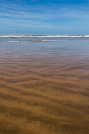 Golden sand of the beach of the Atlantic ocean. Small waves. Blue sky with white clouds, autumn weather. North of Essaouira, Morocco. Reklamní fotografie
