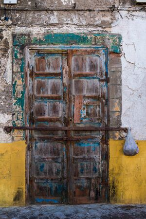 Very old weathered wooden door of a house with damaged colorful facade. Plastic bag hanging on the hasp. Essaouira, Morocco.