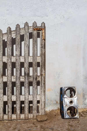 White enlightened wall of a building. Wooden lath opened part of a gate and a broken silver cover of a cooker beside. Essaouira, Morocco. Reklamní fotografie