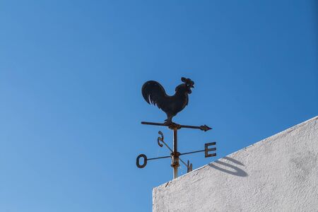 Iron black rooster on a corner of a roof of a building with white facade, together with a compass. Bright blue summer sky. Alvor, Portugal.