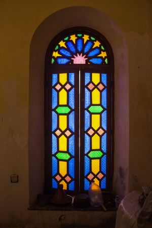 Well-preserved part of an abandoned complex. Interior of a room with a window with colorful vitrage and wooden frame.  Dar Caid Hadji (used also Hajji), Morocco. Archivio Fotografico