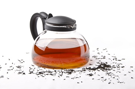 Teapot with black tea on white background and tea leaf