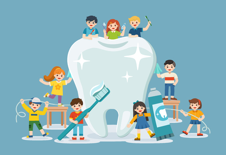 Group of smiling boys and girls standing next to big white tooth holding toothbrush showing healthy clean tooth encouraging teeth hygiene and care.