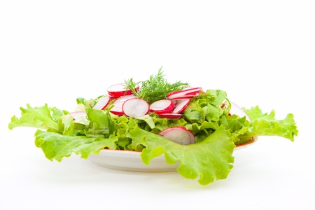 fresh salad of lettuce and radishes in a dish on a white background Stock Photo