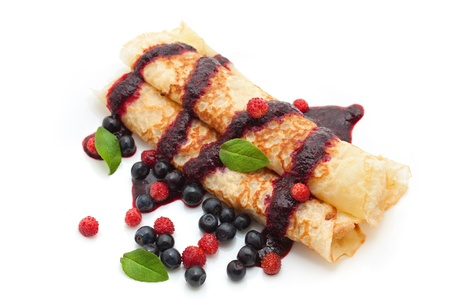 pancakes rolled in a tube with berries, filled with berry sauce on a white background Stock Photo