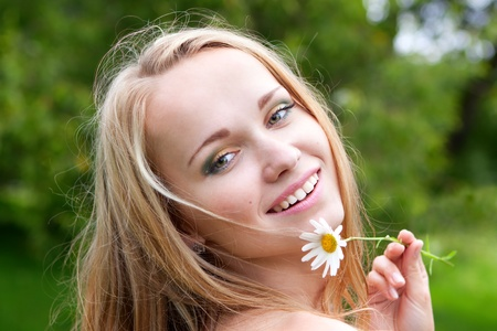 beautiful young woman with camomile, summer day photo