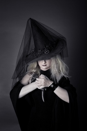 witch with a dagger in his hands, in black clothes and hat photo