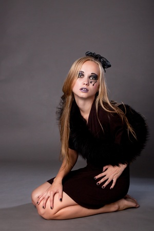 Attractive girl make up as a witch for Halloween sitting on the floor photo