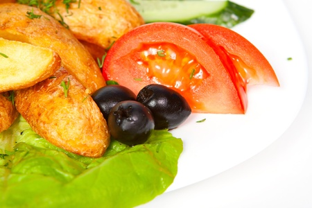 fried potato slices with fresh tomatoes, olives and cucumbers lying on the leaves of lettuce photo