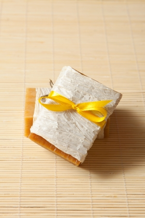 natural soaps tied with yellow ribbon on a bamboo mat Stock Photo - 13646185