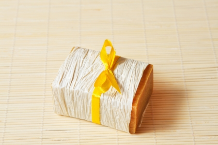 handmade soap tied with yellow ribbon on the mat photo