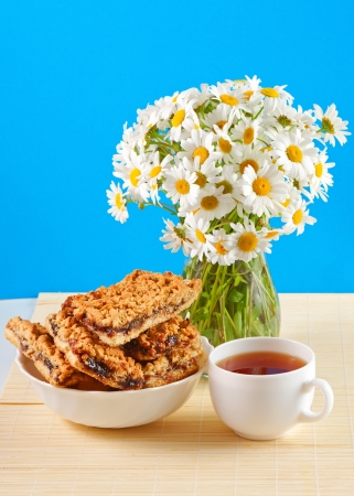 cookies with jam, cup of tea and a bouquet of daisies in the pitcher photo