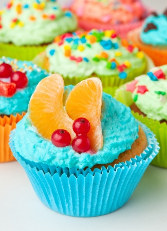 vanilla cupcakes with whipped cream decorated with fruit, berries and sugar confectionery flouring photo