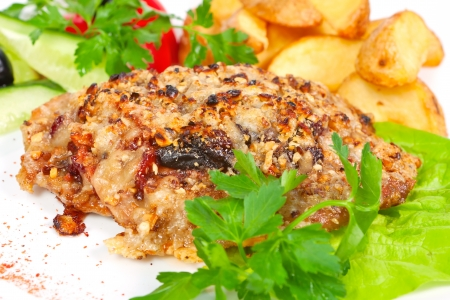 Meat, roast with prunes and peanuts with herbs, lettuce and garnished with fried potatoes photo