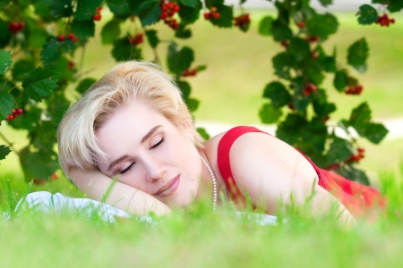 beautiful young woman lying in the grass closing his eyes and dreaming photo
