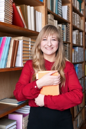 Happy student holding a book, standing against the library shelves photo