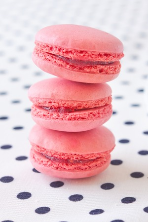 fresh strawberry macaroon stacked on spotted fabric photo