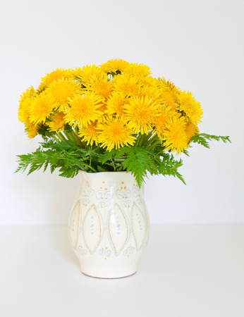 lush bouquet of yellow dandelions in a white cruse photo