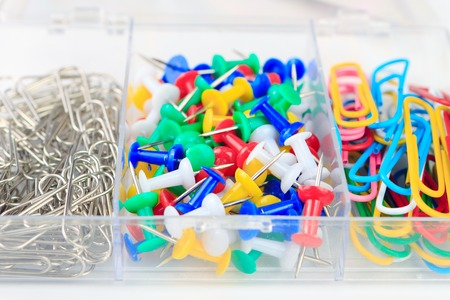 yellow tacks: office supplies in a box, set of stationery, multicolored paper clips and buttons stationery