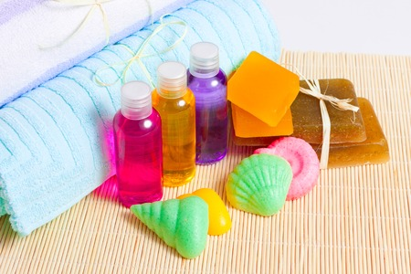 gels: towels, handmade soap and shower gels on a bamboo mat