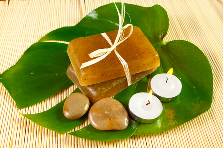 Natural handmade soap with herbs on a green monstera leaf