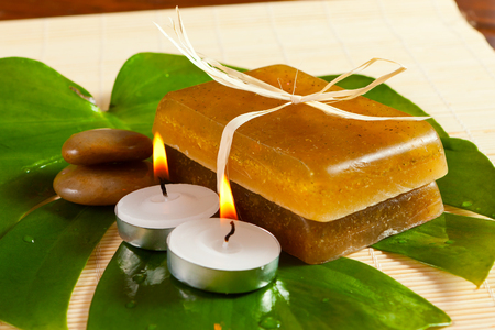 Natural handmade soap with herbs on a green leaf of tropical plant Stock Photo