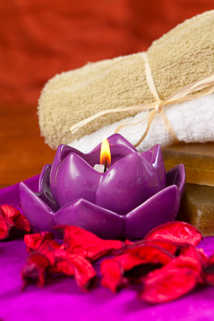 Candle in the shape of lotus and bathing items Stock Photo
