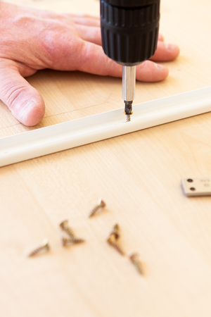 trundle: Drill and screws - the man does the work of assembling furniture Stock Photo