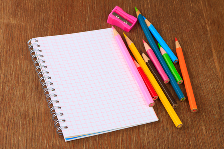 Colored pencils, pencil sharpener and notebook on a wooden background Stock Photo