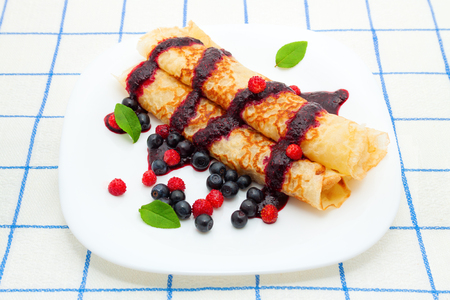 Thin pancakes with berry sauce and blueberries and wild strawberries