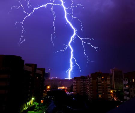Potężne wyładowanie piorunów na sylwetki domów podczas nocnej burzy nad miastem