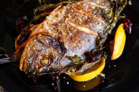 Fried dorado fish with lemon and rosemary close-up