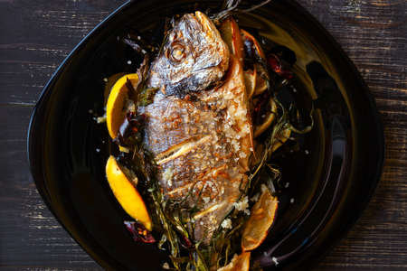 Fried dorado fish with lemon and rosemary close-up on a black wooden background. Stok Fotoğraf