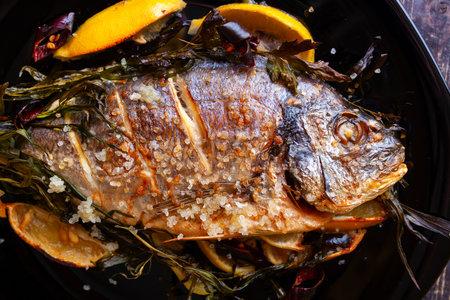 Fried dorado fish with lemon and sea salt close-up on a black background.