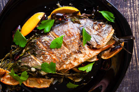 Baked sea bream with tarragon, parsley and rosemary with juicy fresh lemon