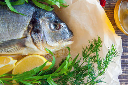 sea gilthead fish prepared for roasting with lemon and fresh herbs