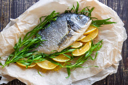Fresh sea bream with lemon and herbs tarragon and dill on paper for baking