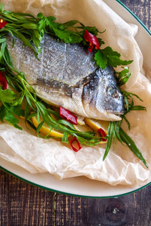Bream with lemon, hot pepper and aromatic herbs prepared for baking