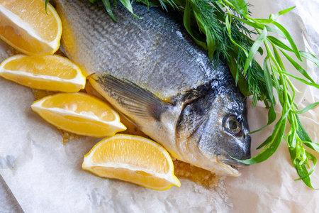 Diet sea dorado fish prepared for baking with lemon and herbs closeup